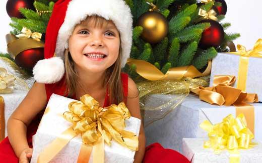Девочка в новогоднем костюме под ёлкой с подарками