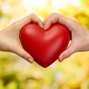 Мужчина и женщина держат одно красное сердечко на двоих