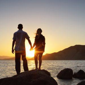 Парень и девушка, взявшись за руки  смотрят на восход солнца